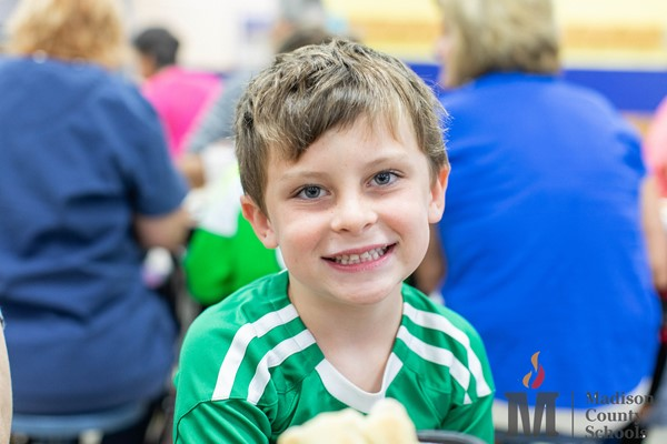 Boy smiling during grandparents lunch day.