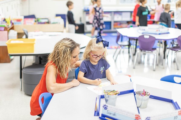 Teacher working with a girl student.