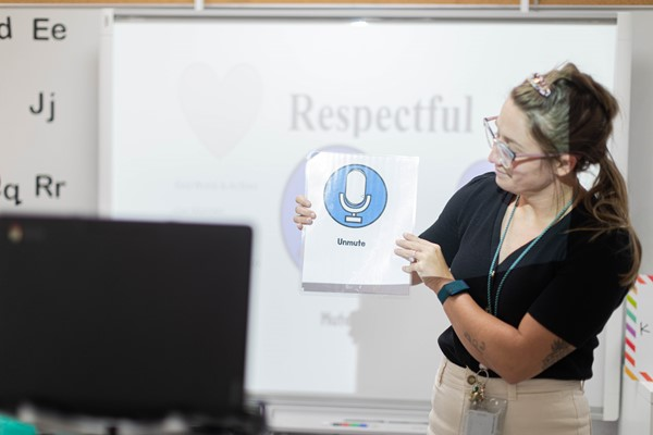 female teacher holding a sign during zoom class