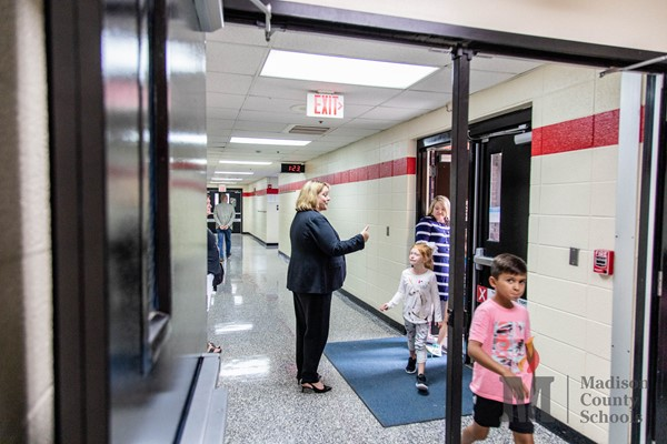 Female principal in the hallway with her students.
